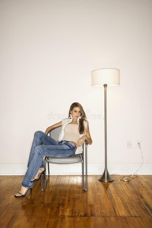 Ung kvinna som sitter i stol. royaltyfri fotografi