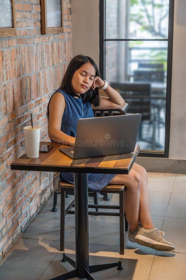 Ung kvinna som sitter med bärbara datorn och stänger hennes ögon arkivbild