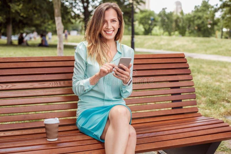 Ung kvinna som sitter på bänk med koppen kaffe som bläddrar smartphonen som ser att skratta för kamera som är gladlynt royaltyfria bilder