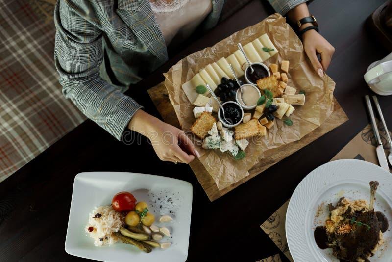 Ung kvinna som sitter på en tabell i restaurangen och äter uppsättningen av ost smakligt mellanmål Härlig portion av mat i kafét arkivfoton