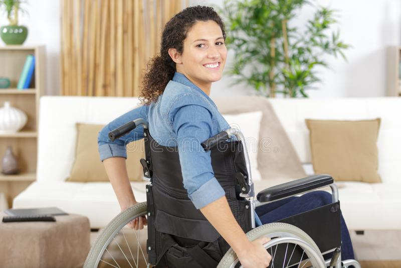 Ung kvinna som sitter på rullstolen royaltyfria foton