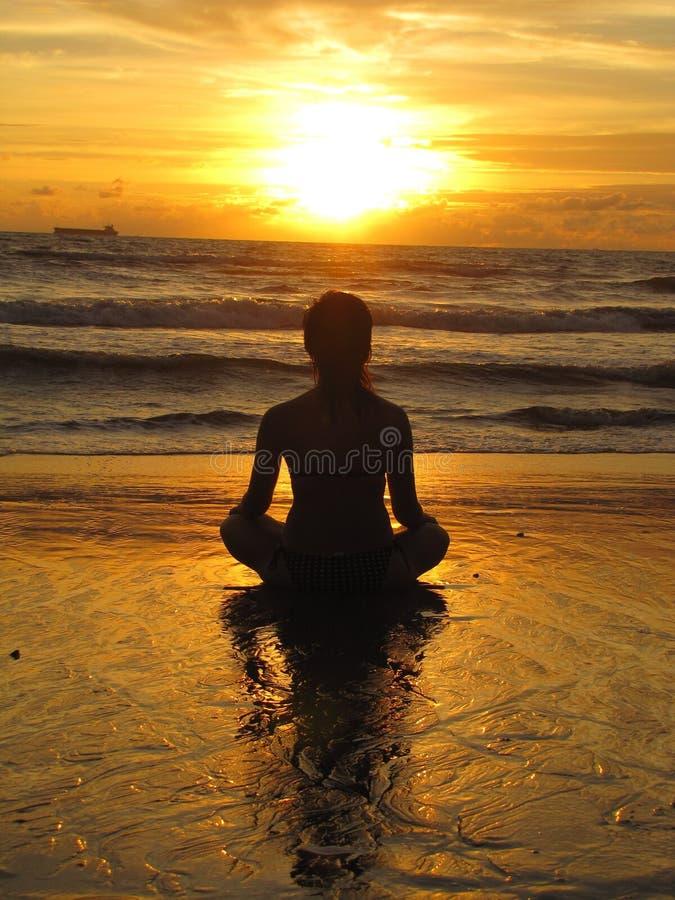 Ung kvinna som sitter på stranden, silhuette vid solnedgången Ung kvinna som tränar yoga utomhus Begreppet harmoni och meditation royaltyfri bild