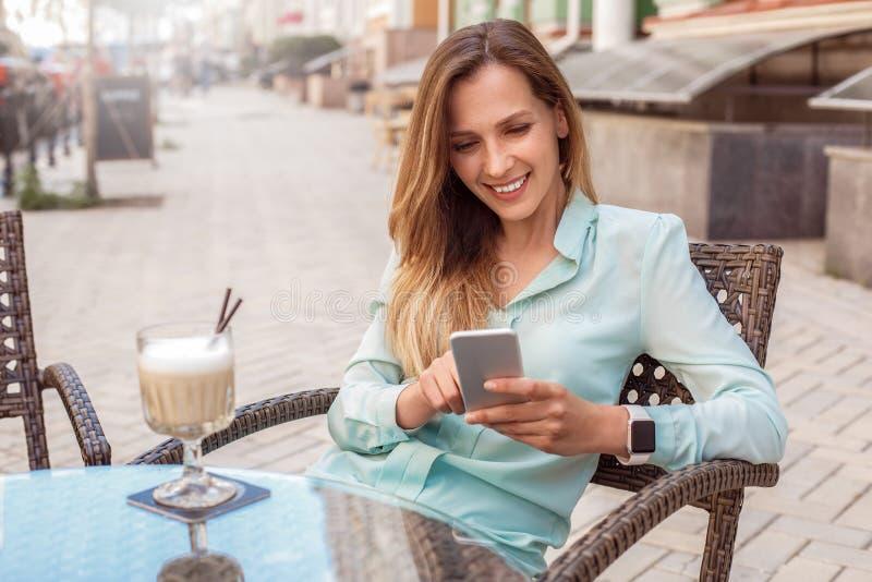 Ung kvinna som sitter på tabellen i kafé med koppen kaffe som spelar leken på att skratta för smartphone som är gladlynt royaltyfri bild