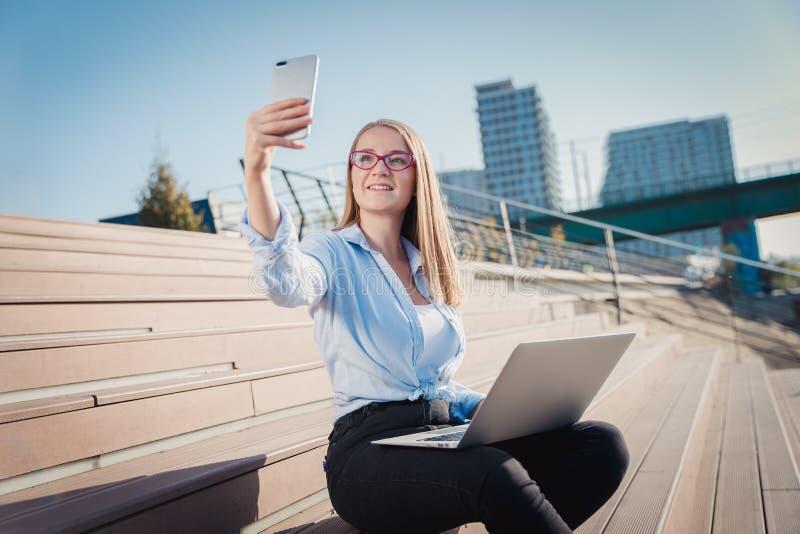 Ung kvinna som sitter på trappan, arbetar på bärbara datorn och gör selfie royaltyfria bilder