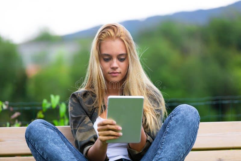 Ung kvinna som sitter utomhus genom att använda en minnestavla royaltyfria bilder
