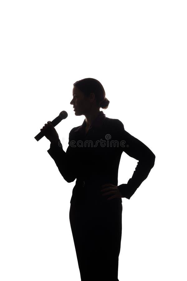 Ung kvinna som sjunger in i mikrofonen royaltyfri foto