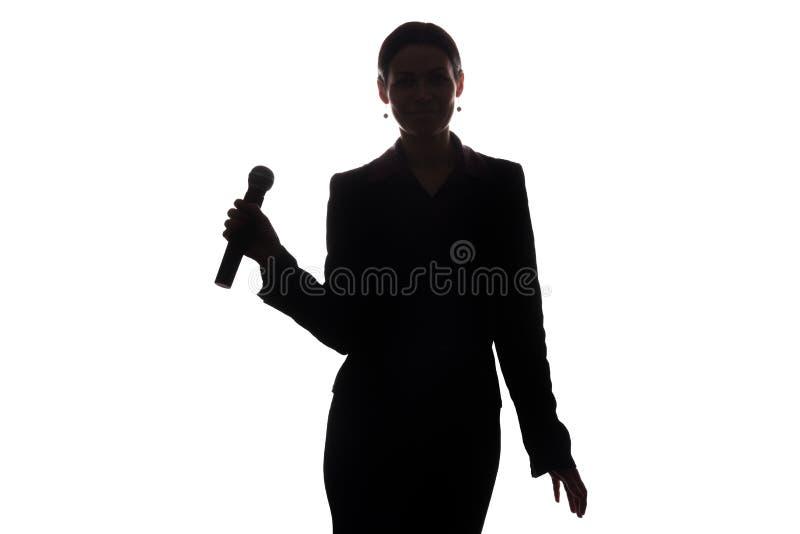 Ung kvinna som sjunger in i mikrofonen royaltyfria foton