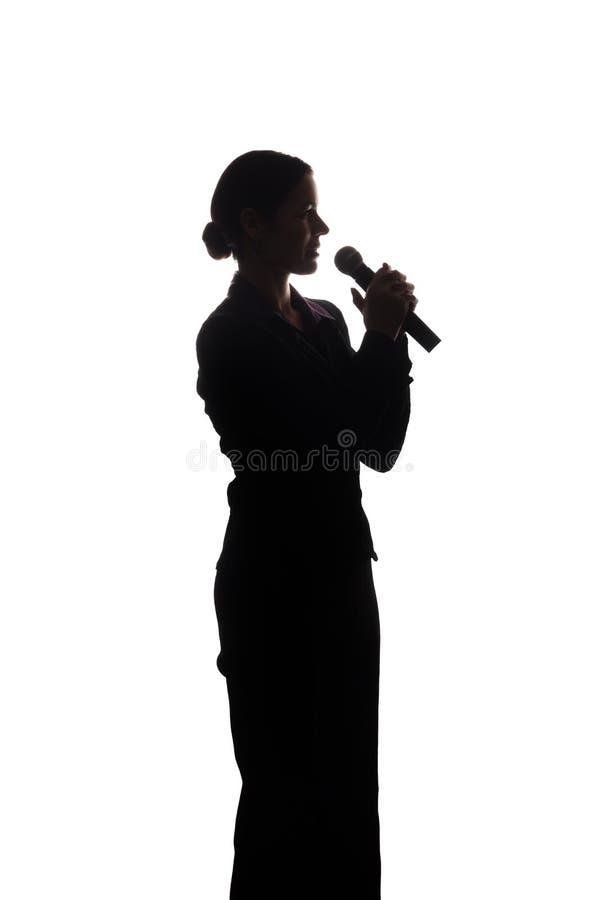 Ung kvinna som sjunger in i mikrofonen royaltyfria bilder