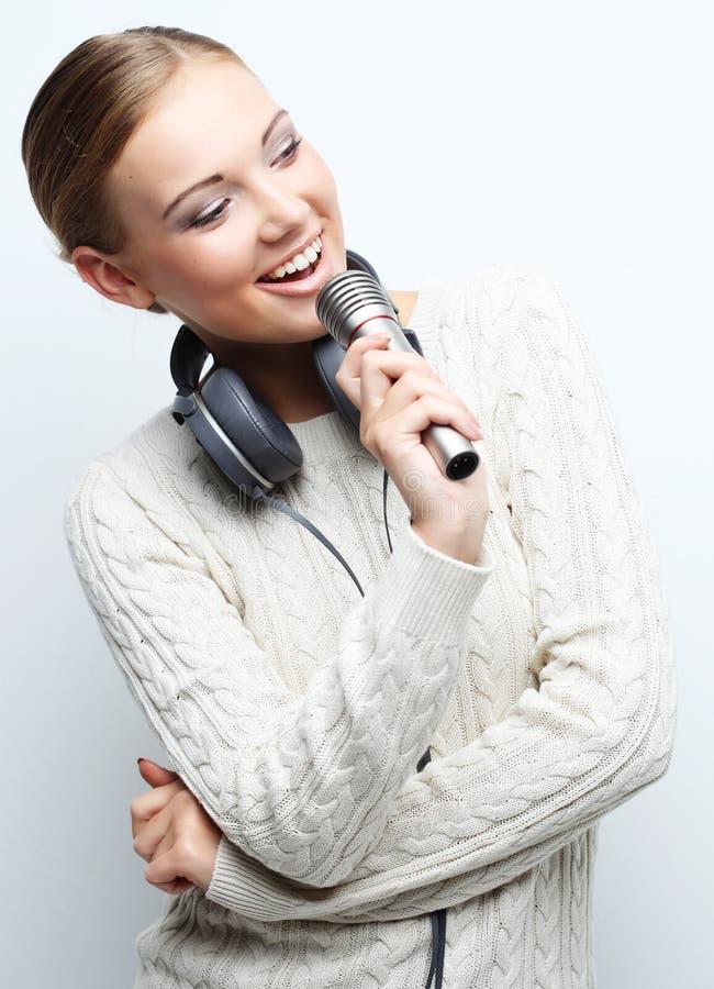 Ung kvinna som sjunger in i mikrofonen med hörlurar i studio på arkivfoto