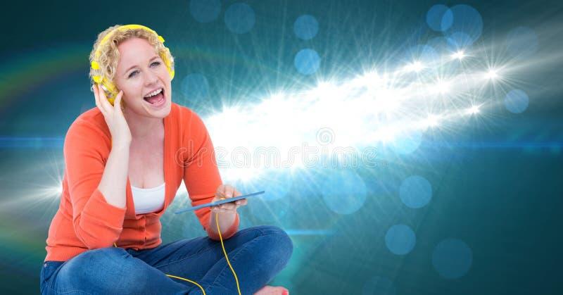 Ung kvinna som sjunger och lyssnar till sånger på hörlurar arkivfoton