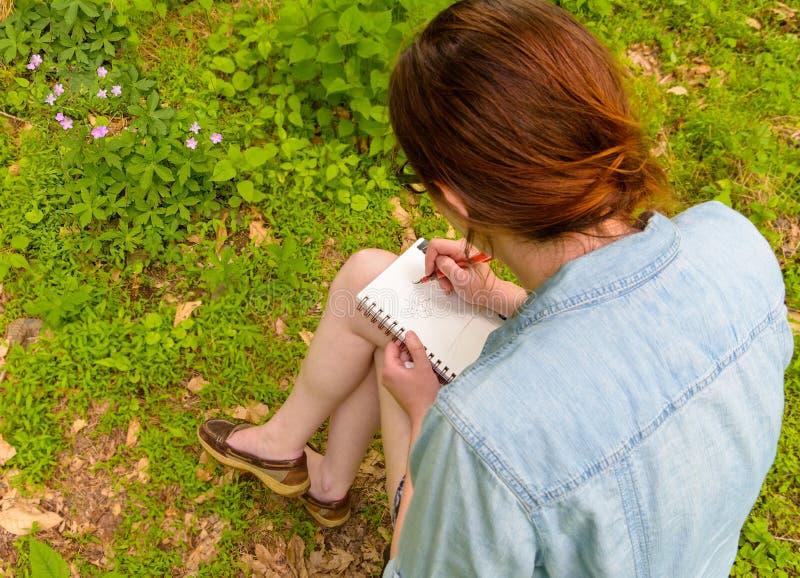 Ung kvinna som skissar blommor i ett fält royaltyfri fotografi