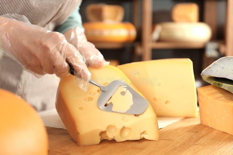 Ung kvinna som skivar läcker ost arkivfoto
