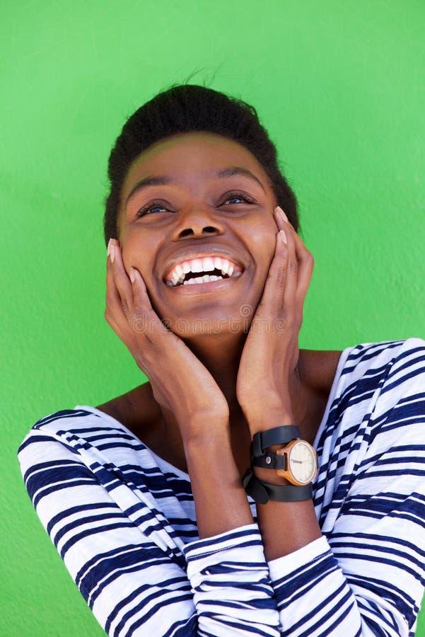 Ung kvinna som skrattar med händer på framsida royaltyfria bilder