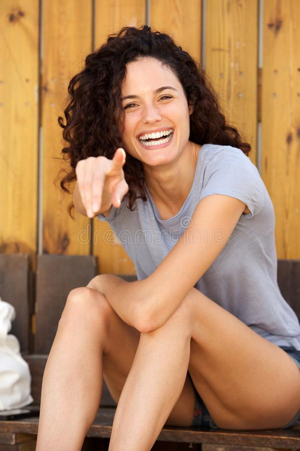 Ung kvinna som skrattar och pekar fingret royaltyfria foton