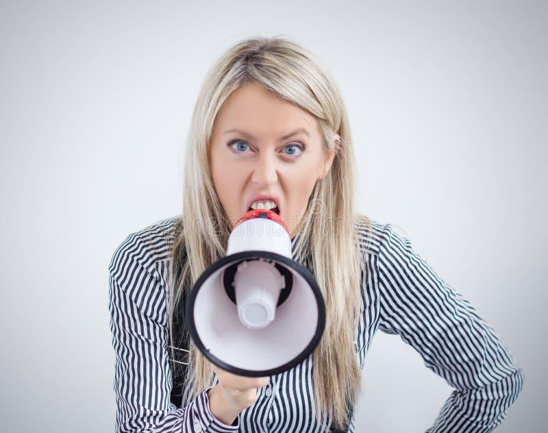 Ung kvinna som skriker på megafonen royaltyfri foto