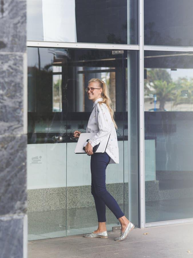 Ung kvinna som skriver in en kontorsbyggnad royaltyfri bild