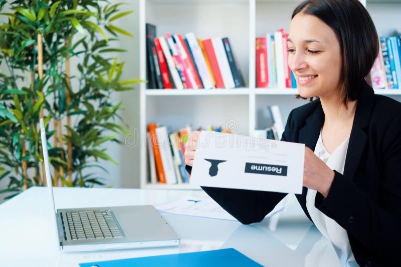 Ung kvinna som skriver hennes CV-meritförteckning för jobbintervju royaltyfria bilder