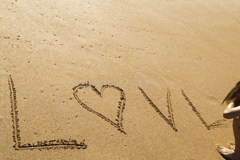 Ung kvinna som skriver ordförälskelsen i sanden av en härlig strand fotografering för bildbyråer