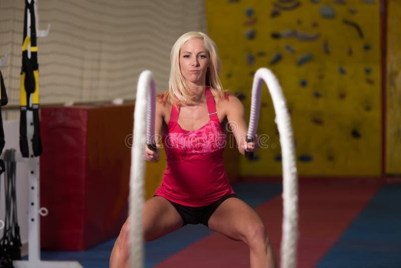 Ung kvinna som slåss rep på idrottshallgenomkörareövningen arkivfoton