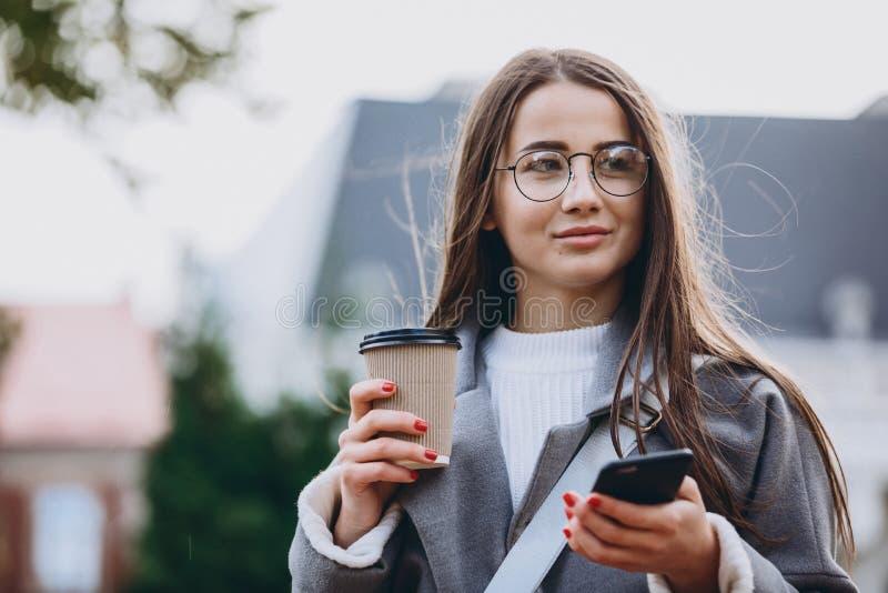Ung kvinna som smsar eller använder smartphonen royaltyfri foto