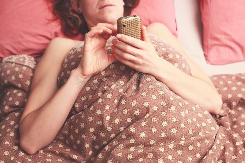 Ung kvinna som smsar i säng royaltyfria foton