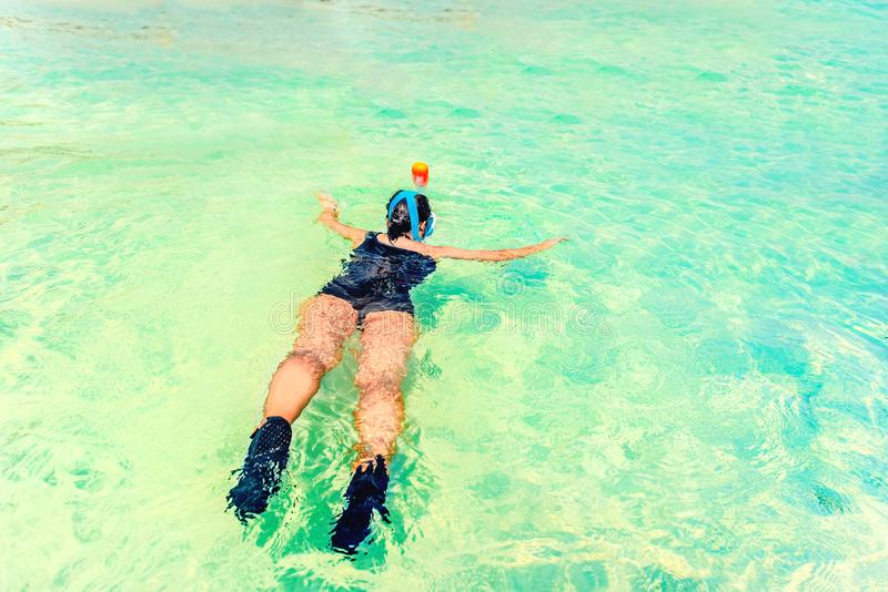 Ung kvinna som snorklar i ett tropiskt hav nära den sandiga stranden på en solig dag arkivbilder