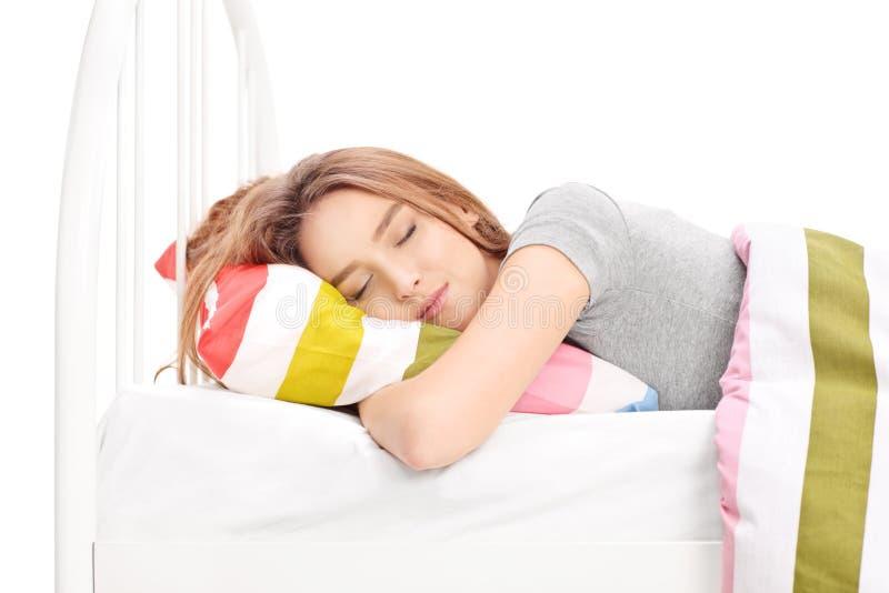 Ung kvinna som sover i en bekväm säng arkivbilder