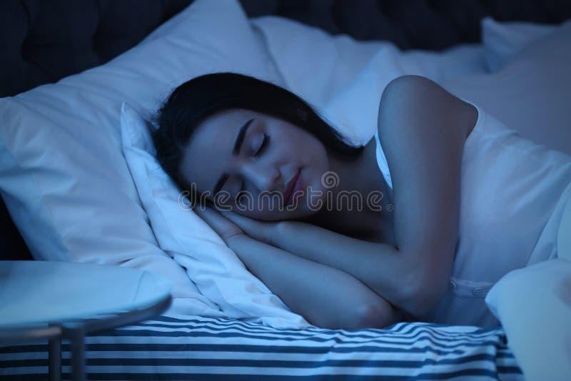 Ung kvinna som sover i säng på natten fotografering för bildbyråer