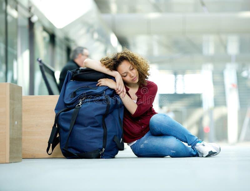 Ung kvinna som sover på flygplatsen arkivfoton