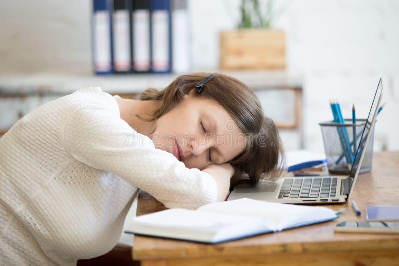 Ung kvinna som sover på kontorsskrivbordet arkivfoto