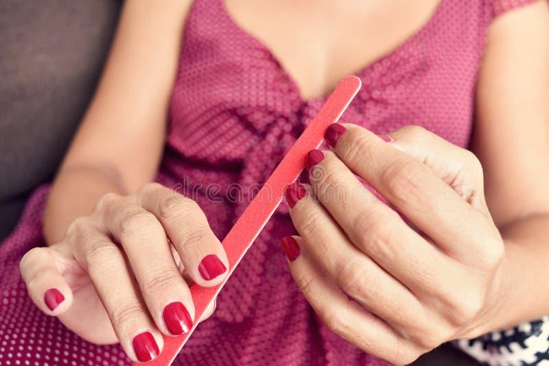 Ung kvinna som sparar hennes fingernaglar arkivfoton