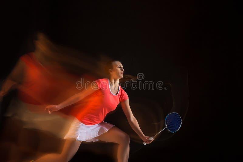 Ung kvinna som spelar badminton över svart bakgrund arkivfoton