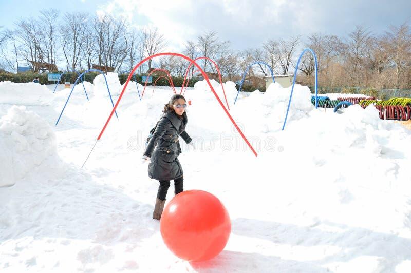 Ung kvinna som spelar bollen på snön fotografering för bildbyråer