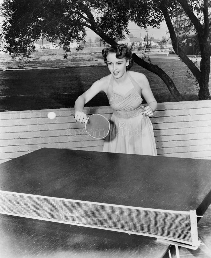 Ung kvinna som spelar bordtennis (alla visade personer inte är längre uppehälle, och inget gods finns Leverantörgarantier som där fotografering för bildbyråer