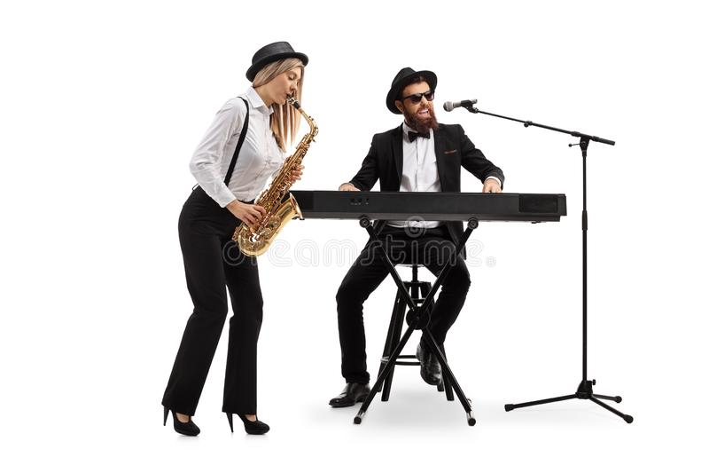 Ung kvinna som spelar en saxofon och en man som spelar tangentbord royaltyfri bild