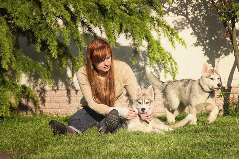 Ung kvinna som spelar med hundkapplöpningen fotografering för bildbyråer