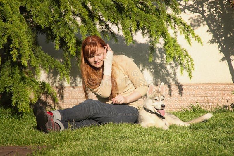 Ung kvinna som spelar med hundkapplöpningen royaltyfri bild