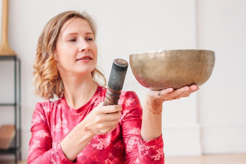 Ung kvinna som spelar på den mässingstibetana sjungande bunken Solid terapi och meditation arkivbilder