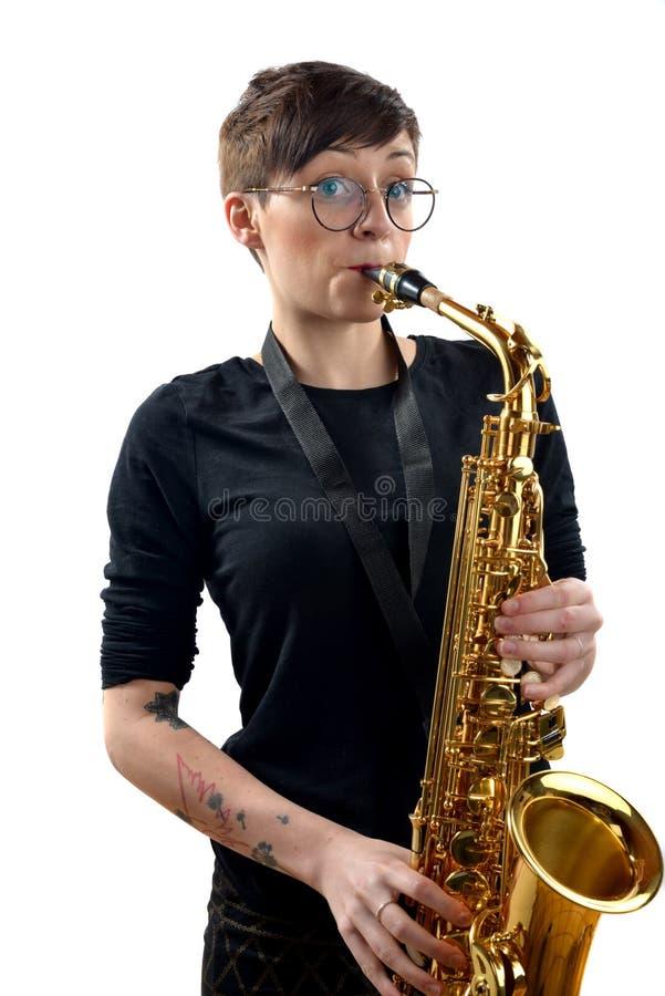 Ung kvinna som spelar saxofonen arkivfoton