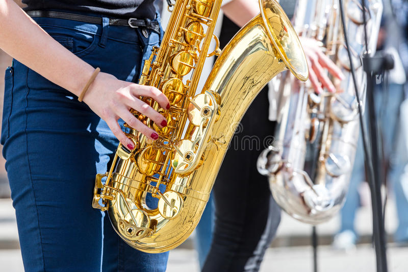 Ung kvinna som spelar saxofonen under gatakapacitet arkivbild