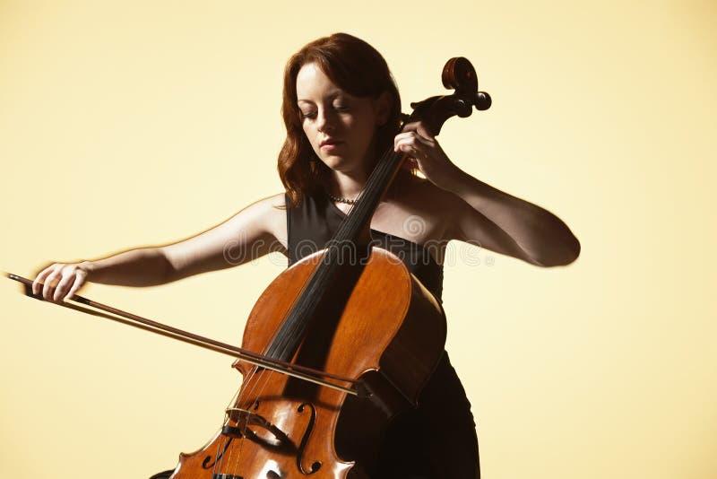 Ung kvinna som spelar violoncellen arkivbilder