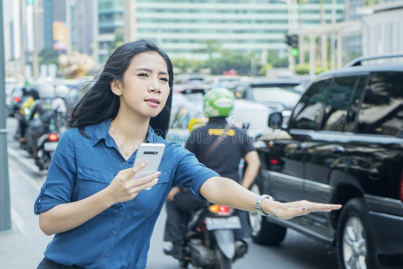 Ung kvinna som stoppar online-taxin royaltyfria bilder