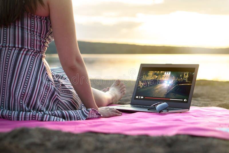 Ung kvinna som strömmar en film med bärbar datordatoren på stranden royaltyfri bild