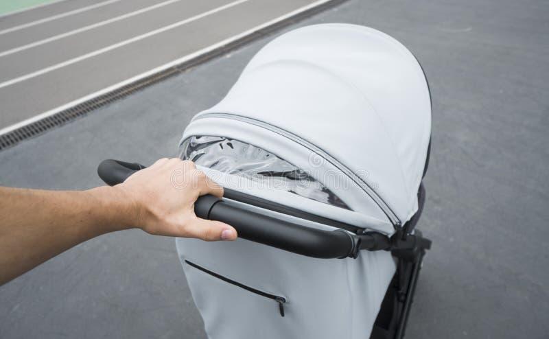 Ung kvinna som strosar en utomhus- vagn Closeup som skjutas av manliga händer med det gråa sittvagnhandtaget Att skjuta för moder arkivfoto