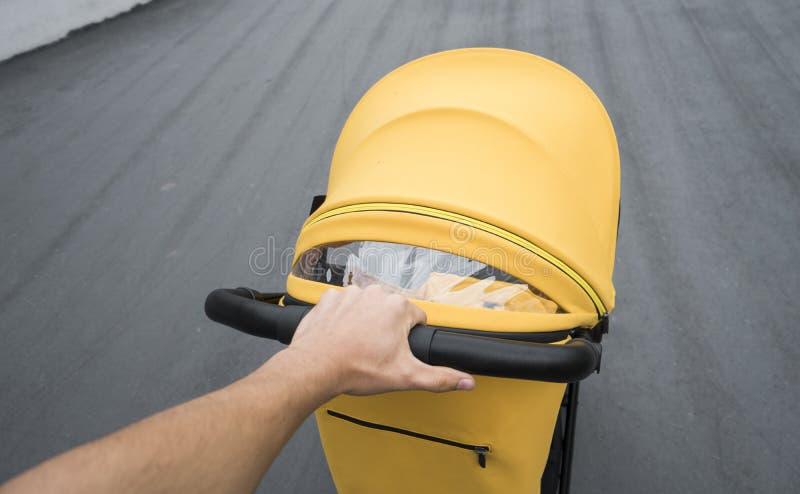 Ung kvinna som strosar en utomhus- vagn Closeup som skjutas av manliga händer med det gula sittvagnhandtaget Skjuta för moder arkivbild