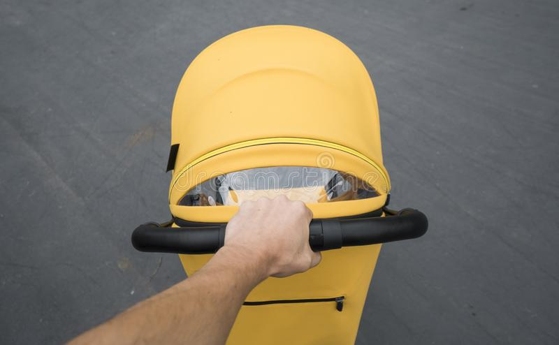 Ung kvinna som strosar en utomhus- vagn Closeup som skjutas av manliga händer med det gula sittvagnhandtaget Skjuta för moder arkivbilder