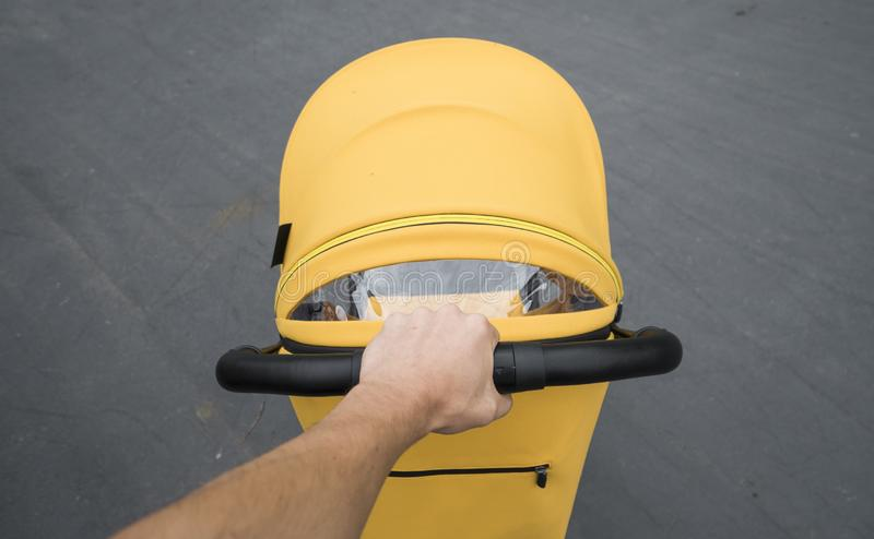 Ung kvinna som strosar en utomhus- vagn Closeup som skjutas av manliga händer med det gula sittvagnhandtaget Skjuta för moder royaltyfri foto