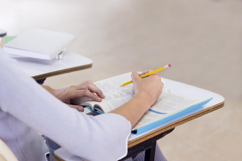 Ung kvinna som studerar för ett prov, studenthänder som skriver i bok på klassrumet Lära och utbildning, högskolabegrepp royaltyfri foto