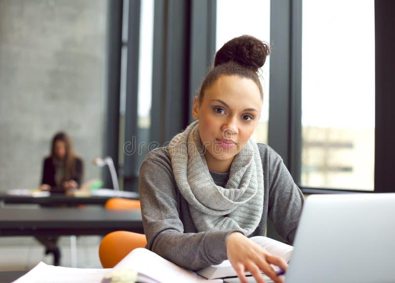 Ung kvinna som studerar i arkiv genom att använda bärbara datorn royaltyfria bilder