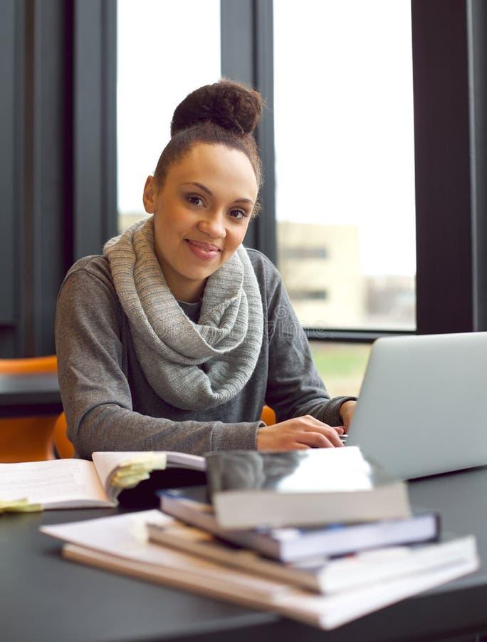 Ung kvinna som studerar på ett skrivbord genom att använda böcker och bärbara datorn royaltyfri foto